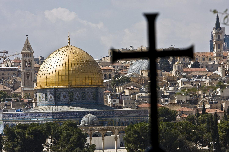 La silueta de una cruz se proyecta sobre la imagen de la Mezquita de la Roca
