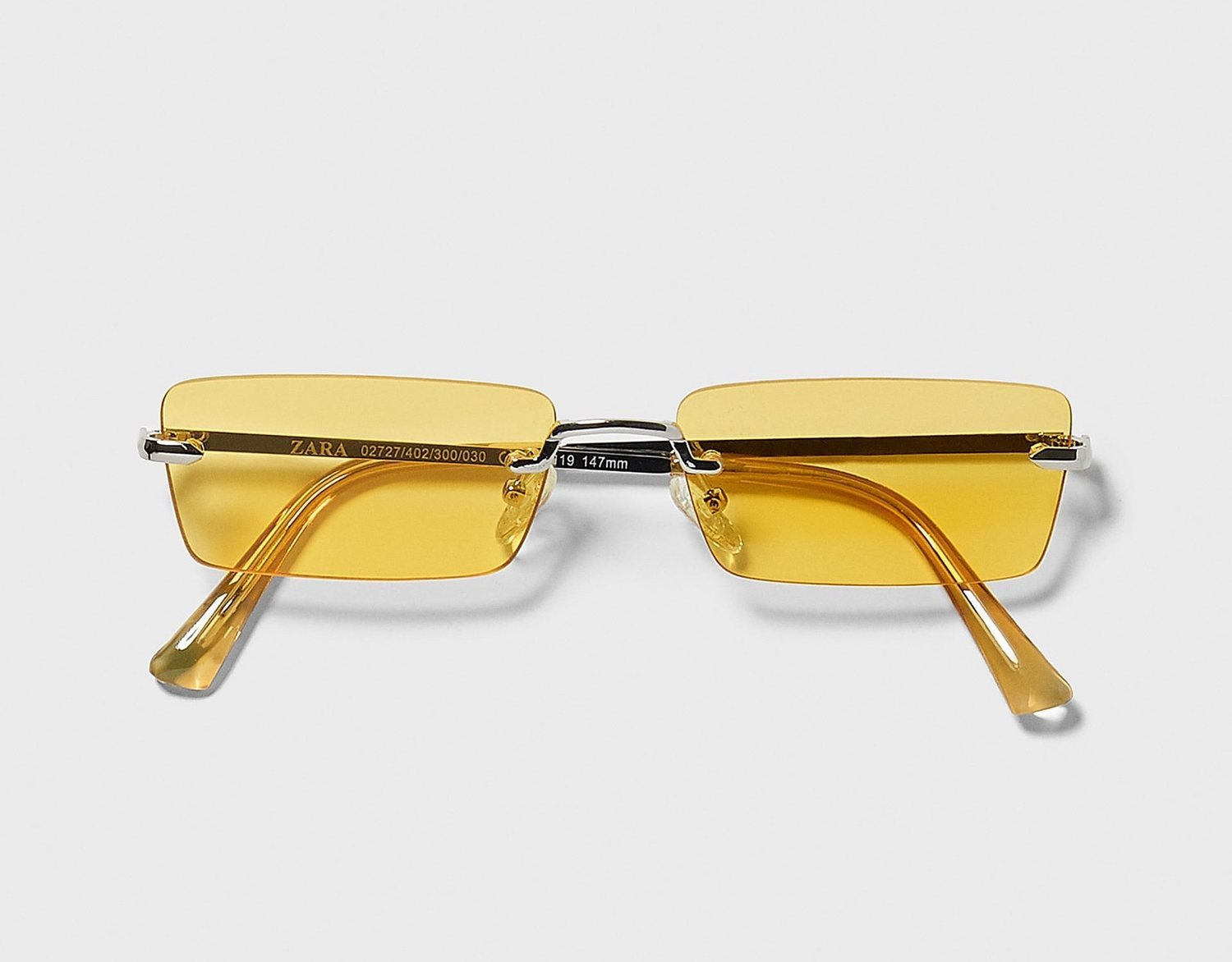Gafas rectangulares con montura al aire y cristal coloreado.