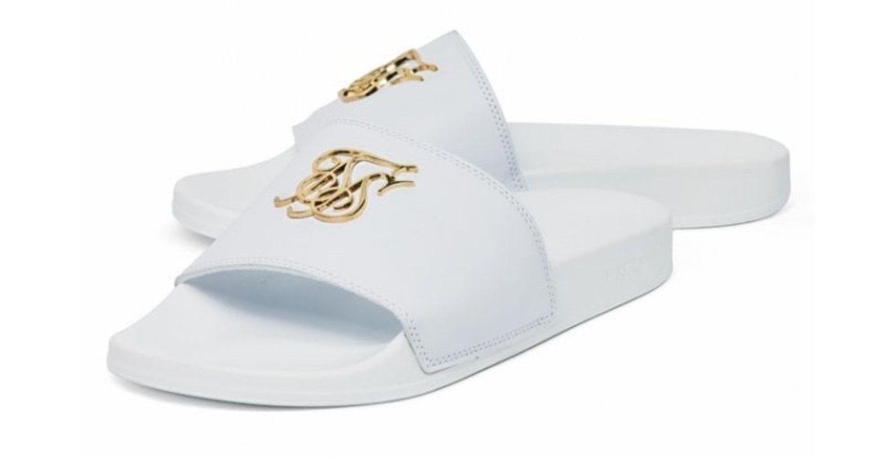 Suela y tira ancha en color blanco, con el símbolo de la marca en dorado